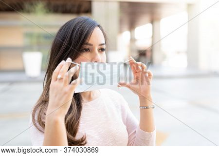 Mid Adult Woman Looking Away While Wearing Face Mask During Coronavirus Crisis In City