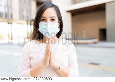 Mid Adult Woman With Hands Clasped Making Awareness To Wear Face Mask During Coronavirus Outbreak