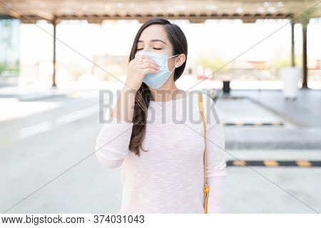 Mid Adult Woman In Face Mask Sneezing While Standing On Footpath In City During Coronavirus