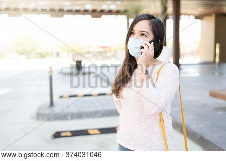 Mid Adult Woman Looking Up While Talking On Mobile Phone During Coronavirus Crisis