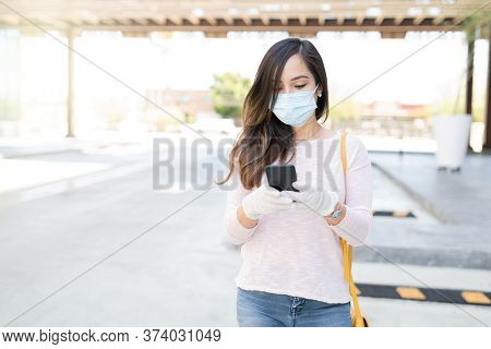 Caucasian Mid Adult Woman Using Smartphone While Standing On Footpath In City During Coronavirus Out