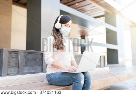 Mid Adult Woman In Face Mask Using Laptop While Sitting On Seat In City During Coronavirus Outbreak