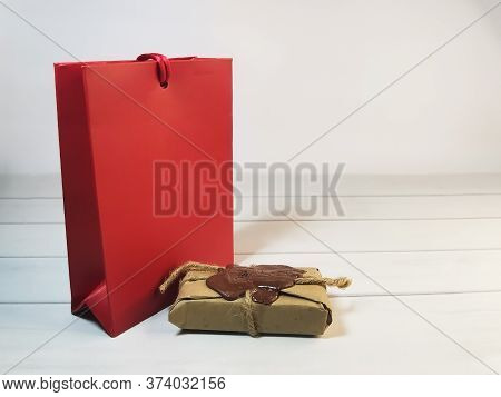 A Red Gift Bag And A Small Package With A Wax Seal, Tied With Twine On Wooden Boards. Romantic Gift,