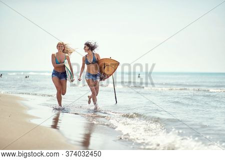 Young girl running to surfing on the beach.Sexy woman with  surfboard at summer.