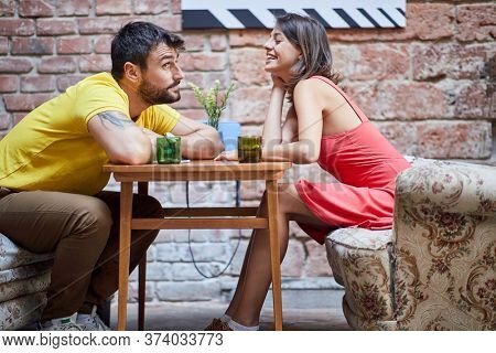 cute young caucasian couple flirting across the table in modern vintage cafe