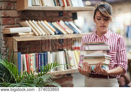 young caucasian female carrying pile of books with both hands trying to blow hair from her face