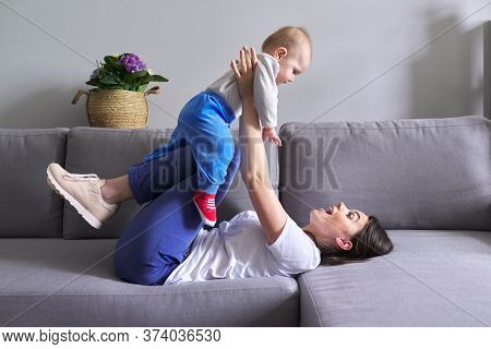 Happy Mother With Toddler Son At Home. Laughing Woman Playing With Baby Lying On Sofa. Family, Child