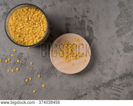 Yellow Lentils In A Glass Jar. The Gray Background.