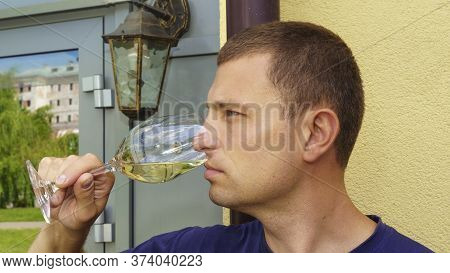 Sommelier Guy Holds A Glass Of White Wine And Appreciates The Taste, An Expert Tastes Wine On A Lamp