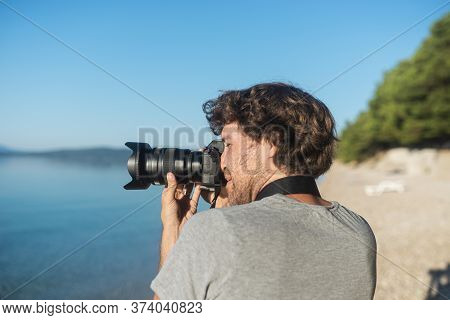Young Male Photographer Taking Photos Of Beautiful Sea And Nature In Early Morning With His Professi