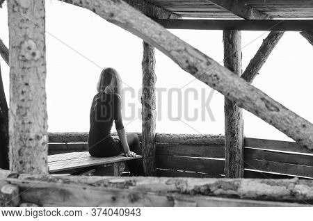 Girl Alone Sits Early In The Morning On A Foggy Day In A Wooden Arbor