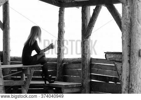 A Girl Sits In A Wooden Arbor On A Foggy Day And Looks Into The Distance