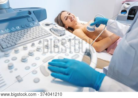 Woman patient having ultrasound scan on modern machine to prevent breast cancer