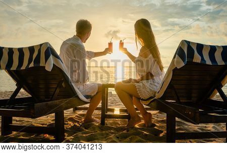young couple drinking cocktails on beach during sunset in deck chairs having vacation or honeymoon in tropics