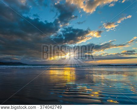 Sunrise over the ocean. Gentle cloud colors are reflected in the ocean water. Light wind causes small ripples in the water. The sun's rays make their way through the light morning clouds.