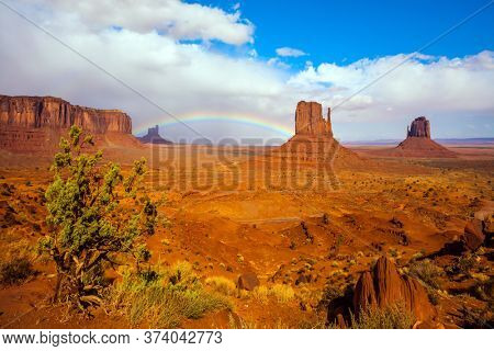 The USA. Magnificent rainbow in the Monument Valley. The Mittens. Huge masses of red sandstone - outliers on the Indian Navajo Reservation. Concept of active and photo tourism