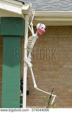 Covid-19 Pandemic Skeleton Decoration Wearing A Red Bandana Mask While Clinging Onto Roof Eaves