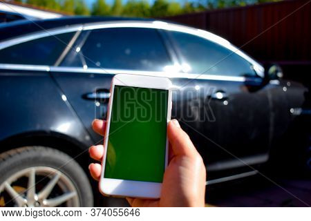 Phone In Hand On A Background Of A Car. Call A Car Mechanic. Car Rental. Search For Information On T