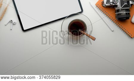 Modern Worktable With Blank Screen Tablet, Tea Cup, Camera, Stationery And Copy Space