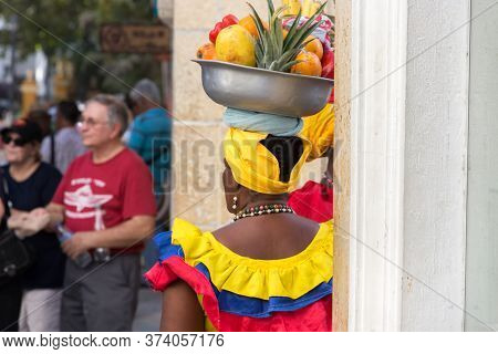 Cartagena, Colombia - January 23th, 2018: Rear View Of A Fruit Vendor Palenquera With A Metal Basket