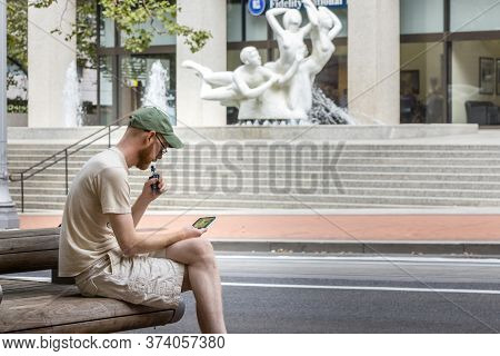 Portland, Oregon, Usa - September 9th, 2017: A Man Is Sitting Smoking An Electronic Cigarette And Lo