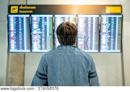 Travel Insurance Concept. Asian Man Tourist Looking At Arrival Departure Board In Airport Terminal.