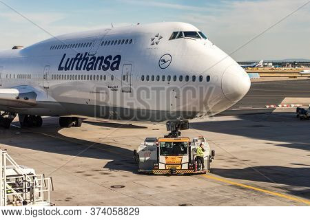 Frankfurt, Germany - July 3th, 2018: An Airplane Tractor Is Pushing Back A Boeing 747 Of Lufthansa A