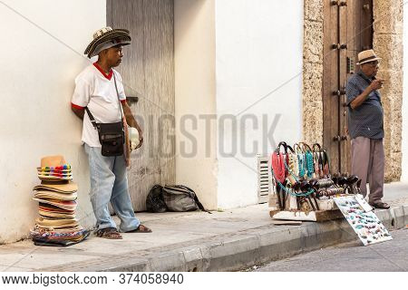 Cartagena, Colombia - January 23th, 2018: A Hat Street Vendor And A Necklaces And Souvenirs Vendor S