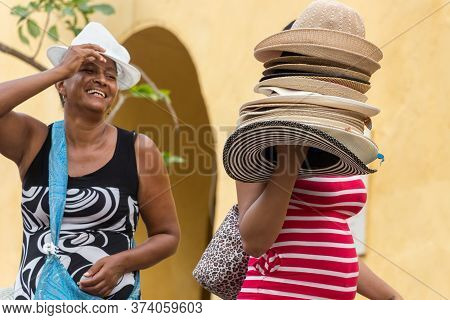 Cartagena, Colombia - January 23th, 2018: A Hat Street Vendor And A Female Customer Trying A Hat Smi