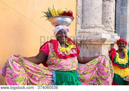 Cartagena, Colombia - January 23th, 2018: A Woman Palenquera With A Metal Basket With Fruits Posing