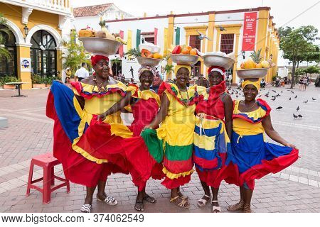 Cartagena, Colombia - January 23th, 2018: Five Palenqueras With A Metal Basket With Fruits Are Posin