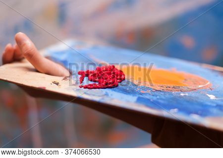 Artist Holding Wooden Palette With Red Paint In Art Workshop. Modern Artwork Paint On Canvas, Creati
