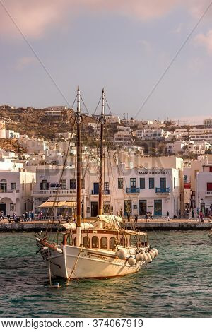 Mykonos, Greece - October 12th, 2018: A Wooden Sailboat And The City Waterfront In The Background Of