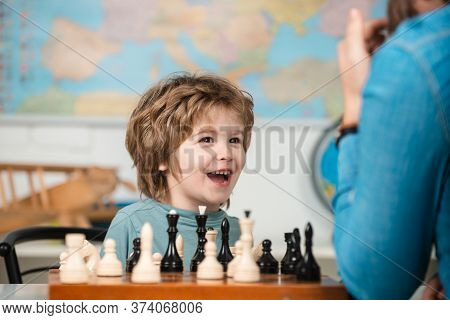 Child Chess School. Cheerful Smiling Little Boy Sitting At The Table And Evincing Gladness While Pla