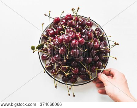 Large Ripe Cherry Berries With Leaves On White Plate And Famale Hand On White Background. Top View.