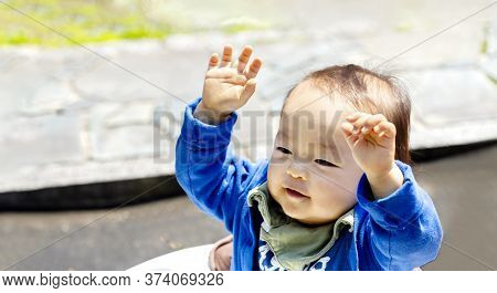A Young Kid Boy In The Garden With Both Arms In The Air. A Baby Raises Both Hands.