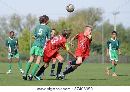 KAPOSVAR, HUNGARY - SEPTEMBER 22: Marton Kiss (green 5) in action at the Hungarian Championship under 15 game between Rakoczi (green) and Mezga FC (red) September 22, 2012 in Kaposvar, Hungary.