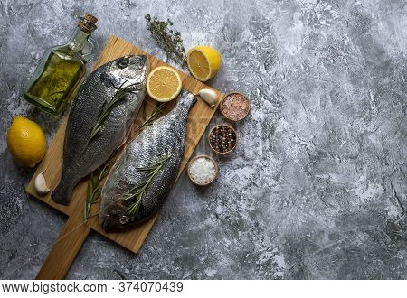 Fresh Fish Dorade Or Sea Bass On Cutting Board With Ingredients For Cooking. Top View With Copy Spac