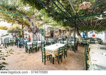Hydra, Greece - October 4th, 2018: A Traditional Greek Taverna With Wooden Green Chairs In The City