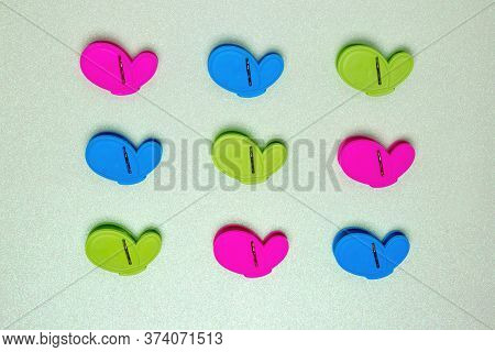 Colourful Set Of Nine Plastic Clothespins Or Pegs On A Light Green Sparkling Background With Copy Fi
