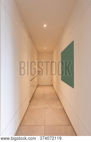 Interior of a long corridor of an apartment. At the bottom a closed door