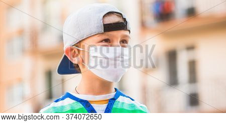 Child Wearing A Medicine Mask Outdoors. Coronavirus Epidemic. Boy With Protection Facemask. Boy In A