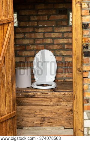 A Simple Village Toilet With A Huge Roll Of Toilet Paper.large Roll Of Toilet Paper In The Toilet