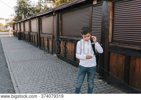 Teenage Boy Take Out A Wireless Headphones And Put Then Into The Ears. Young Boy In White Shirt With