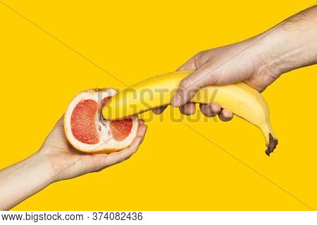Erotic Banana And Donut In The Hands As A Symbol Of The Penis And Vagina Isolated On A Yellow Backgr