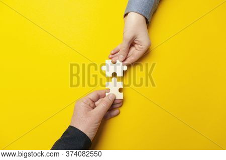 Two Hands Connect Puzzles On A Yellow Background. Cooperation And Teamwork In Business. Collaboratio