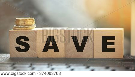 Word Save On Wooden Cubes On A Computer Keyboard With Coins. Money Saving And Taxes Saving Business
