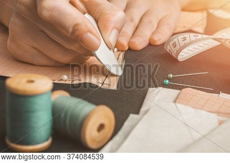 Closeup Of The Hand Of Professional Seamstress Making Chalk Marks On Black Fabric Using A Pattern. T