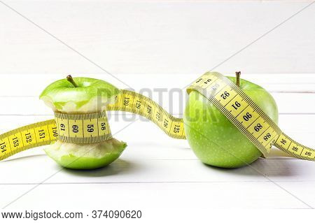 Green Apple And Apple Stump With Yellow Centimeter Tape On White Wooden Background. Concept Sport, D