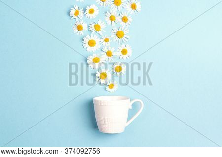 White Cup And Chamomile Flowers On A Blue Background. Chamomiles Come Out Of The Cup Like Steam. Cha